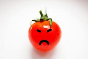 怒っている表情をした赤い顔のトマト