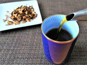 生薬と湯のみに注ぐ漢方薬の煎じ液