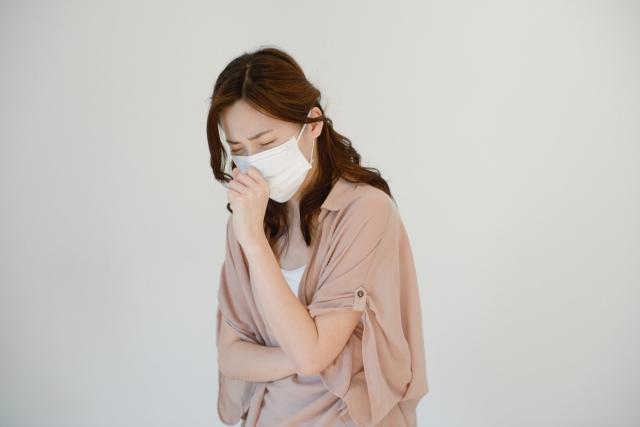 咳き込むマスクをした女性